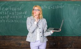 Woman wear eyeglasses holds laptop surfing internet. Educator smart clever lady with modern laptop searching information. Chalkboard background. Online stock images