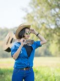 Woman wear hat and carry her guitar in grass field Stock Images