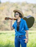 Woman wear hat and carry her guitar in grass field Stock Photos