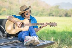 Woman wear hat and playing guitar on pickup truck Stock Photography