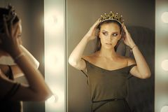 Woman wear jewelry crown at mirror. Beauty queen with glamour look in dressing room. Girl princess and reflection in. Mirror. Woman beauty, makeup and look royalty free stock image