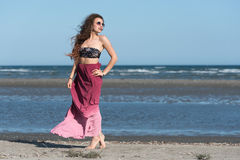 Woman wear long skirt and top, standing on the beach Stock Photos