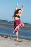 Woman wear long skirt and top, standing on the beach Stock Image
