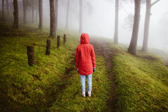 Woman wear red coat  turn back on path way with fog Royalty Free Stock Photos