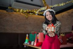 Woman wear red dress and santa claus hat showing golden gift box on hand in restaurant. concept of Christmas party royalty free stock photography