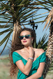 Woman wear a short dress leaning on palm trees Royalty Free Stock Photo