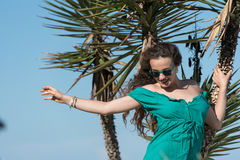 Woman wear a short dress leaning on palm trees Royalty Free Stock Image