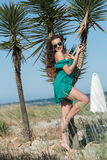 Woman wear a short dress leaning on palm trees Stock Photography