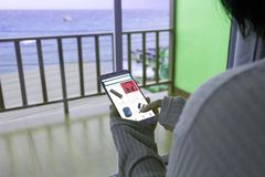 Woman wear sweaters use a mobile phone on the hotel`s balcony by the sea. stock images