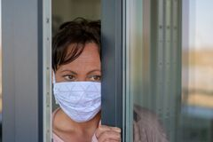 Free Woman Wearing A Face Mask Peering Around Anxiously Royalty Free Stock Photography - 179149457