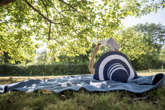 Woman Wearing A Straw Hat In Summer Nature Reading A Book