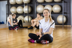 Woman Wearing Activity Tracker While Sitting On Floor In Gym Royalty Free Stock Images