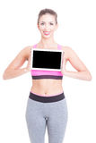 Woman wearing aerobic clothes holding tablet gadget. Young woman wearing aerobic clothes holding tablet gadget and smiling on white with copy text space royalty free stock images
