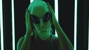 Woman wearing an alien mask. Portrait of blonde straight hair woman wearing an alien mas - surreal, eccentric concept stock footage