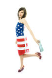 Woman wearing an American flag. Beautiful young woman wearing an American flag walks with a bag in her hand Royalty Free Stock Images