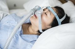 A woman wearing anti-snoring chin straps Stock Images