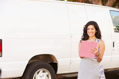 Woman Wearing Apron With Clipboard In Front Of Van Royalty Free Stock Photos