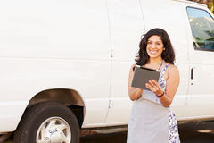 Woman Wearing Apron With Digital Tablet In Front Of Van Stock Photography
