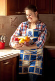 Woman wearing apron holding fresh bowl with fruits Stock Image
