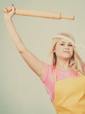 Woman wearing apron holding rolling pin Royalty Free Stock Image