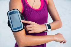 Woman wearing arm band and smart watch at beach Stock Photos