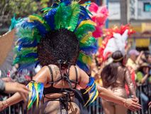Woman wearing Aztec feather head wear, marching down a parade royalty free stock image