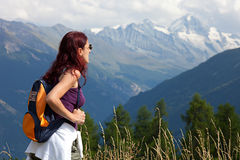 Woman wearing a backpack hiking the Alps. Stock Images