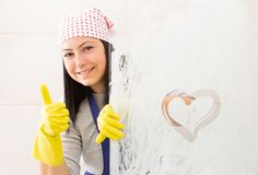 Woman showing thumb up gesture from behind shower glass with heart drawing. Woman wearing bandana and blue apron showing thumb up gesture from behind shower royalty free stock image