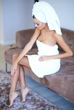 Woman Wearing Bath Towel Touching Her Leg. Woman Wearing Bath Towel Sitting on Sofa and Touching Her Leg royalty free stock image