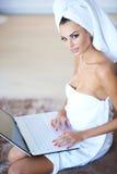 Woman Wearing Bath Towel Using Laptop Computer Stock Photos