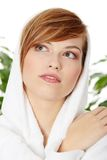 Woman wearing bathrobe. Young blond teen woman wearing bathrobe. Green leafs in background royalty free stock photos