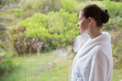 Woman wearing bathrobe against blurred plants Stock Image