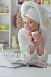 Woman wearing  bathrobe with laptop Stock Image