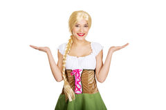 Woman wearing Bavarian dress with open hands. Royalty Free Stock Photography