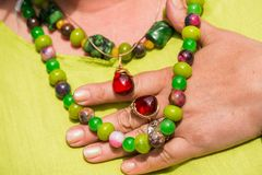 Woman wearing beautiful gemstone necklace and golden ring with amber. Jewelry made of coral, olivine and agate stones. Powerful energy of healing crystals Stock Photography