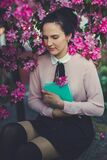 Woman Wearing Beige Long Sleeve Shirt Sitting Beside Purple Petaled Flower Stock Photos
