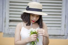 Woman Wearing Beige Sun Hat and White Sleeveless Top Holding White Flowers stock image