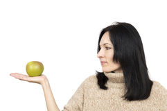Woman wearing beige sweater holding apple. Isolated over white Royalty Free Stock Images