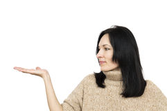 Woman wearing beige sweater holding arm palm up. Isolated over white Royalty Free Stock Photos