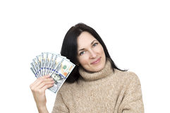 Woman wearing beige sweater holding money. Isolated over white Stock Image