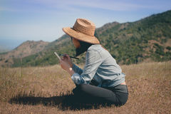 Woman Wearing Beige Wicker Hat Sitting on Brown Grass during Daytime Stock Photography