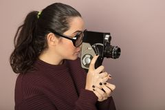 Woman wearing big glasses holding old vintage film camera. Attractive woman photographer wearing nerdy glasses peering into the viewfinder of a vintage 8mm film Stock Images