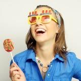 Woman wearing big sunglasses holding lollipop Royalty Free Stock Photos