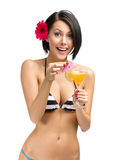 Woman wearing bikini and flower in hair drinks cocktail Royalty Free Stock Photo