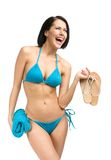 Woman wearing bikini and handing towel and thongs Royalty Free Stock Photos