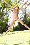 Woman Wearing Bikini Jumping In Garden Royalty Free Stock Photos