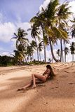 Woman Wearing Bikini Laying on Seashore Stock Image