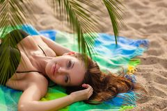 Woman wearing bikini lying on cover Royalty Free Stock Images