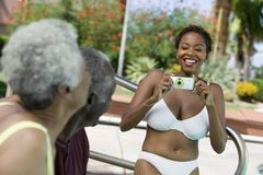 Woman wearing bikini photographing senior couple outdoors. Stock Image