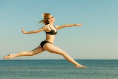 Woman wearing bikini playing, jumping near sea Stock Photography